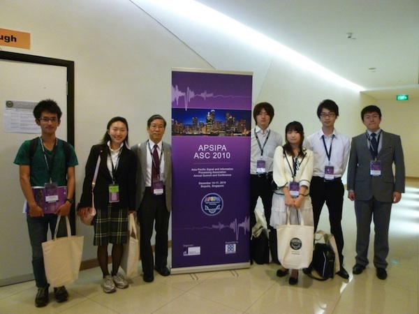 Prof. Nishihara and 6 undergraduate students at the entrance of the conference site
